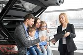View From Side Of Happy Family Buying New Comfortable Black Car In Auto Salon. Handsome Husband Sign poster