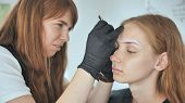 Permanent Makeup. Permanent Tattooing Of Eyebrows. Cosmetologist Applying Permanent Make Up On Eyebr poster