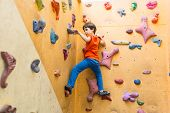 Boy Climbing On Artificial Boulders Wall In Gym poster