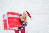 Winter Delivery Service. Woman Carrying A Big Present Isolated On Snow Winter Background. Portrait O poster