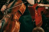 Symphony orchestra on stage, hands playing cello. Shallow depth of field, vintage style. poster