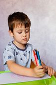 Little Boy Drawing With Color Pencils. There Are Many Colored Pencils In The Boys Hands. Small Boy  poster