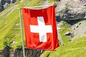 Waving National Flag Of Switzerland With Blurred Alpine Landscape In The Background. White Cross On  poster