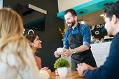 Smiling Waiter Serving Coffee To Young Customers At Restaurant poster