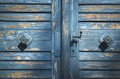 Rustic Wooden Door With Shriveled Blue Paint Close-up On Doorknobs. Antique Blue Wood Gate. Aged Woo poster