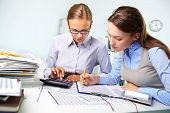 foto of diligent  - Concentrated business women reviewing accounting report - JPG