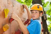 Young guy with  climbed equipment on the top of climbing wall.