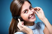 attractive teen girl listening to music on headphones and winking, portrait over blue