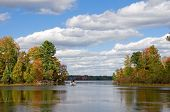 image of pontoon boat  - Photograph of a beautiful northwoods lake in the autumn season being enjoyed by a group heading out into the waters on a pontoon boat - JPG