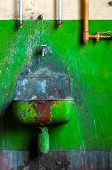 stock photo of lavabo  - Old industrial lavabo with green background closeup photo - JPG