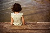 foto of pier a lake  - Lone little girl sitting on pier - JPG