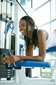 stock photo of derriere  - woman at the gym doing exercises on a machine for her bottom - JPG