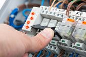 stock photo of fuse-box  - Hand of an electrician turning on a fusebox - JPG