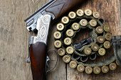 stock photo of cartridge  - vintage hunting gun with cartridges on wooden background - JPG