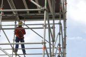 stock photo of scaffold  - worker on a scaffold no face visible - JPG