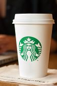 SCARSDALE, NY - SEPTEMBER 15, 2013: A tall Starbucks coffee in front of a woman working on a laptop