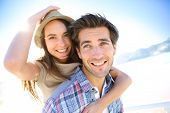 image of piggyback ride  - Man giving piggyback ride to girlfriend at the beach - JPG