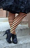 stock photo of black heel  - Legs and feet of woman in black and orange stocking with black high heels - JPG