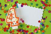 Number four birthday candle on green background