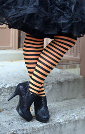 picture of stocking-foot  - Legs and feet of woman in black and orange stocking with black high heels - JPG