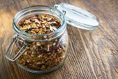 stock photo of mixture  - Homemade granola in open glass jar on rustic wooden background - JPG