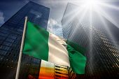stock photo of nigeria  - Nigeria national flag against low angle view of skyscrapers at sunset - JPG