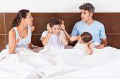 foto of conflict couple  - family conflict arguing parents in a bed - JPG