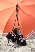 pic of stilettos  - black stiletto heels and necklace with orange umbrella on a cracked earth - JPG