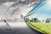 stock photo of sustainable development  - Engineer try to save environment by pulling a banner of new green city - JPG