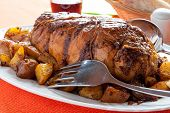 image of frizzle  - a tasty roast with baked potatoes on a table with a tablecloth orange - JPG