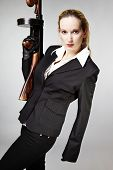 "picture of tommy-gun  - Mafia style fashion studio portrait - nice young woman posing with ""Tommy"" gun for figure and portrait photos in retro criminal style.