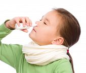 pic of snot  - Cute girl spraying her nose with nasal spray isolated over white - JPG