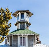 stock photo of cupola  - An old cupola on a home under blue skies of wood and green shingles - JPG