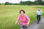 foto of retirement  - Happy asian seniors couple biking in the park - JPG