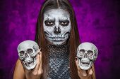 stock photo of day dead skull  - Young woman in day of the dead mask skull face art with two skulls in hands - JPG