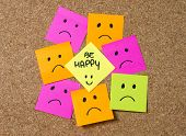 foto of angry smiley  - smiley cartoon face expression on yellow post it note surrounded by sad and depressed faces on cork message board in happiness versus depression and smile against adversity concept - JPG
