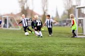 foto of young boy  - Young kids during a boys soccer match on green soccer pitch - JPG