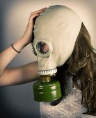 image of rubber mask  - Profile of woman wearing gas mask with her hand on her head - JPG