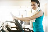 image of cardio exercise  - Attractive young woman smiling and doing cardio exercise on treadmill at gym - JPG
