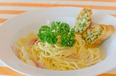 picture of carbonara  - Spaghetti Carbonara with bacon and garlic bread on dish - JPG