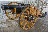 stock photo of artillery  - Old medieval artillery canon before a stone wall - JPG