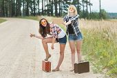 picture of country girl  - Happy girls hitchhike with cardboard on country road - JPG