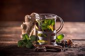 stock photo of mint leaf  - Herbal tea in a glass cup and fresh mint leaves on a wooden board