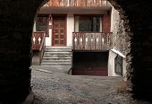 foto of italian alps  - Arched view of old house with wooden balcony in the medieval town Bormio - JPG