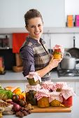 image of pickled vegetables  - Portrait of happy young housewife with jars of pickled vegetables - JPG