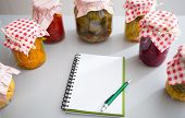 picture of pickled vegetables  - Notepad among jars of pickled vegetables on table - JPG