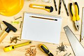 foto of carpentry  - Planning a Project in Carpentry and Woodwork Industry Notebook and Assorted Woodwork and Carpentry Tools on Pinewood Workshop Table - JPG