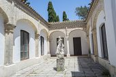 stock photo of carthusian  - Cartuja monastery courtyard with sculpture of a saint in the center Jerez de la Frontera C - JPG