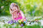 stock photo of baby easter  - Adorable curly toddler girl in a pink summer dress playing with Easter eggs during egg hunt in a sunny garden with first white spring flowers - JPG