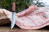 foto of slaughter  - Slaughterer knife and pieces of pig over wooden trough - JPG